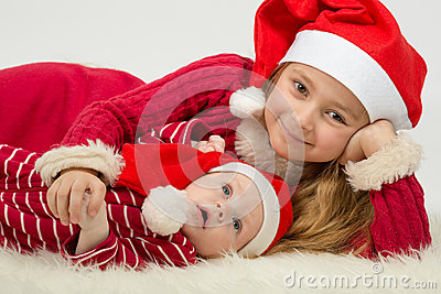 Little girl with baby boy lie in the hats of Santa Claus