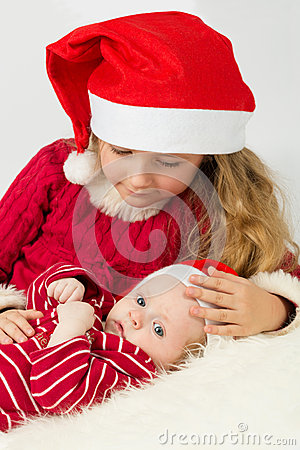 Little girl with baby lie in the hats of Santa Claus