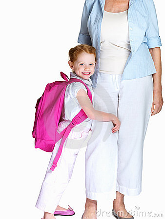 Little girl with bagpack embracing her grandmother