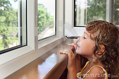 Little girl on balcony, look from window