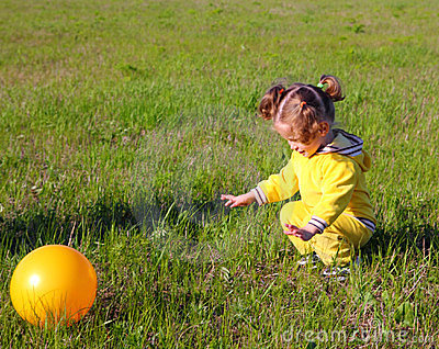 Little girl with ball on meadow