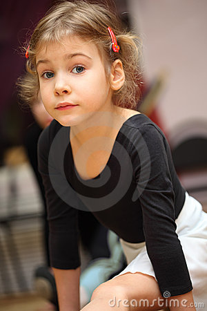 Little girl in ballet class sits on string