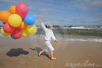 Little girl  with balloons on the beach