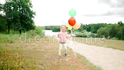 Little girl with balloons in the park stock video