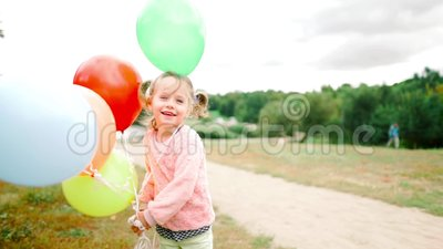 Little girl with balloons in the park stock footage