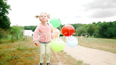 Little girl with balloons in the park stock video footage