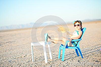 Little Girl In Bathing Suit With Fan In Hot Desert