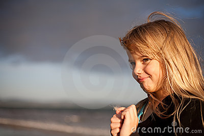 Little girl on beach with dandelion flower