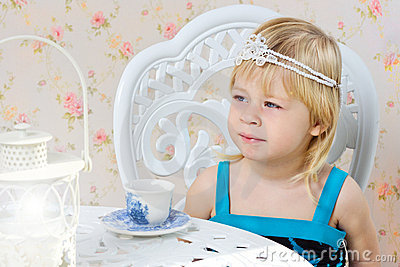 Little girl in a beautiful dress drinking tea