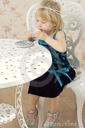Little girl in a beautiful dress drinks tea