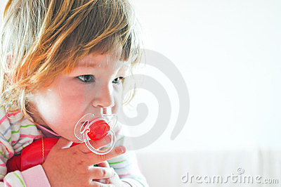 Little girl in bed with red pacifier