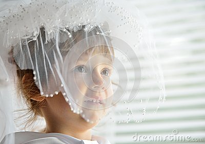 A little girl behind veil