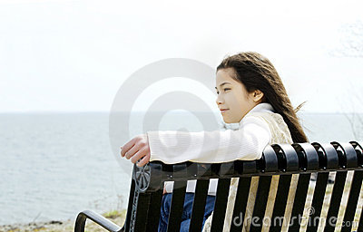 Little girl on bench by lake shore