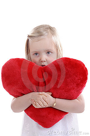 Little girl with big red heart shaped pillow