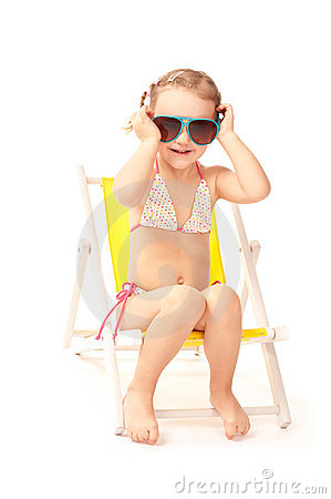 Little girl in big sunglasses sitting on deckchair