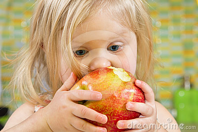 Little girl biting an apple