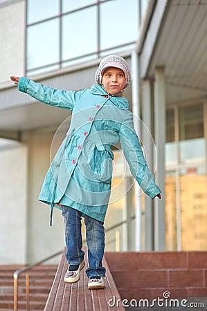 Little girl in blue coat walking on