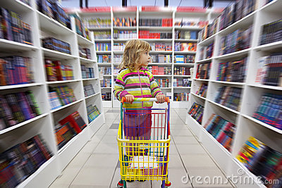 Little girl in bookshop, with cart for goods