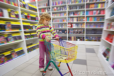 Little girl in bookshop, with cart for purchases