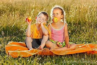 Little girl and boy eating apple