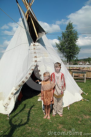 Little girl and boy in front of tee-pee