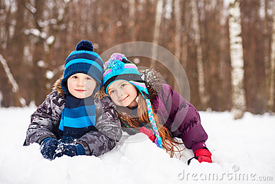 Little girl and boy lie nearby on snowdrift