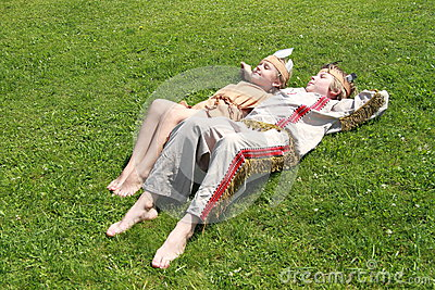 Little girl and boy sleaping on grass