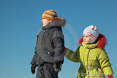 Little girl and boy standing at snow