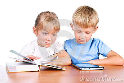 Little girl and boy using digital pad and book