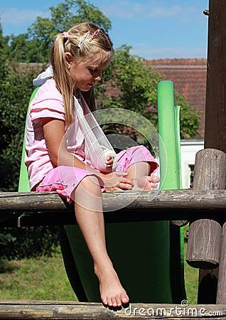 Little girl with broken hand on slide
