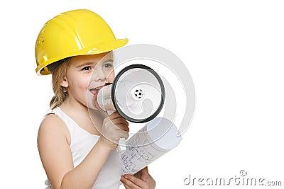 Little girl builder in yellow helmet screaming into the loudspeaker