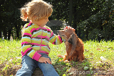 Little girl caress dachshund outdoor