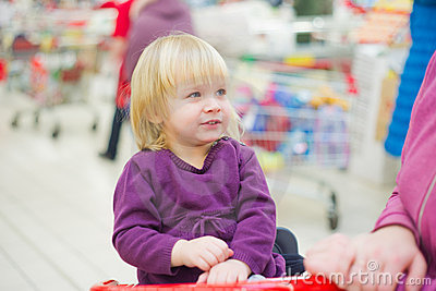 Little girl on cart in supermarket with mother