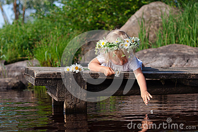 Little girl in chamomile wreath is dropping petals into the water
