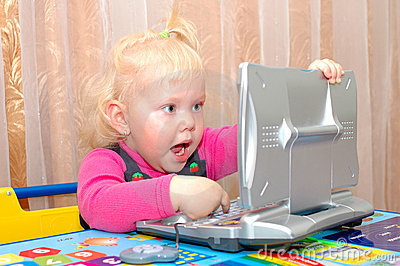 Little girl with child s computer (notebook).