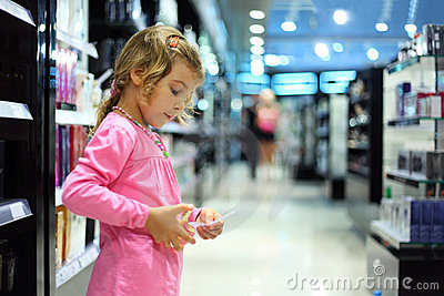 Little girl choose perfume in perfume shop