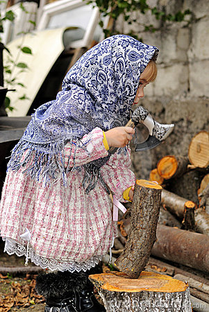 The little girl  chops firewood an axe
