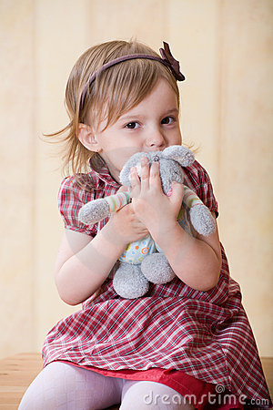 Little girl clasp toy rabbit to one s bosom
