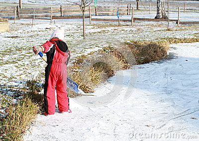 Little girl cleaning ice on pond