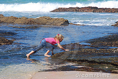 Little girl climbing rocks on beach