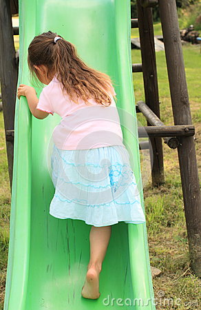 Little girl climbing a slide