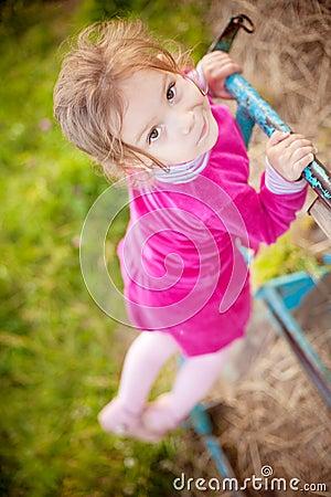 Little girl climbs on horizontal