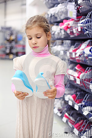 Little girl considers gym shoes and stands near shelves
