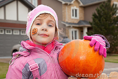 Little girl costs in court yard with pumpkin