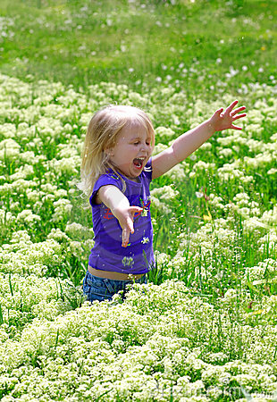 Little girl costs in a grass outdoors