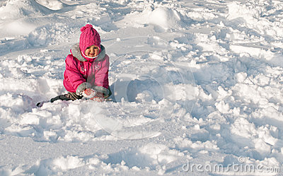 Little girl crawling on snow