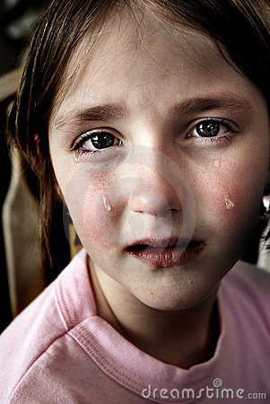 Portrait of little girl crying with tears rolling down her cheeks.
