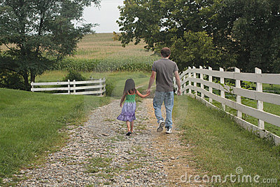 Little girl and dad walking on path