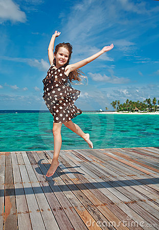 Little girl dancing on the wooden sundeck