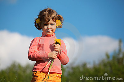 Little girl with dandelion against sky